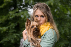 Young sad pretty blonde woman in city park. Small yorkshire terrier is on her hands. Royalty Free Stock Image