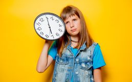 Young sad teenage girl with clock. Portrait of young sad teenage girl with clock on yellow background royalty free stock photography