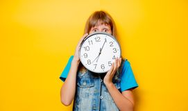Young sad teenage girl with clock. Portrait of young sad teenage girl with clock on yellow background stock photos