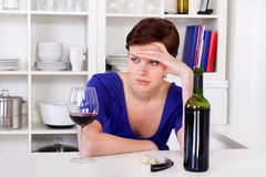Young sad thinkful woman drinking a glass of red wine. Young sad thinkful woman sitting with a glass of red wine in her kitchen stock image