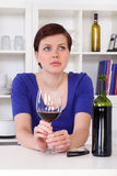 Young sad thinkful woman drinking a glass of red wine. Young sad thinkful woman sitting with a glass of red wine in her kitchen Royalty Free Stock Photos