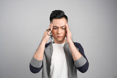 Young sad thoughful asian man having headache after work. Stock Image