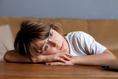 Young sad tired schoolboy, almost sleeps on desk Stock Photos