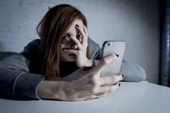 Young sad vulnerable girl using mobile phone scared and desperate suffering online abuse cyberbullying. Being stalked and harassed in teenager cyber bullying stock photo