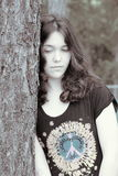 Young sad woman. Sad young woman depressed leaning on tree sepia Stock Photo