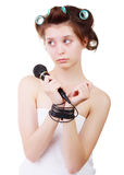 Young sad woman in a bath towel and hair curlers with his hands tied wire microphone. Royalty Free Stock Images
