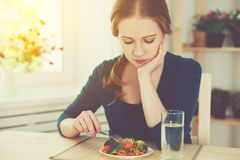 Young sad woman eats vegetables at home in the kitchen Stock Images