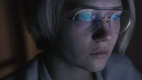 Young sad woman in glasses flips news feed in computer in dark room stock footage