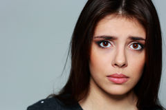 Young sad woman on gray background Stock Photo