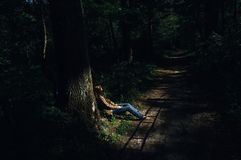 The Young Sad Woman Siting Alone Under the Tree Near Footpath with Shadow Lines in the Gloomy Forest stock image