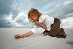 Young sad woman kneeling in the desert on sky background. Stock Image