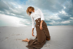 Young sad woman kneeling in the desert on sky background. Royalty Free Stock Images