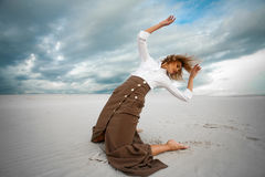 Young sad woman kneeling in the desert on sky background. Stock Photography