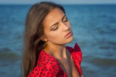 Young sad woman near the sea on a sunset Royalty Free Stock Photography