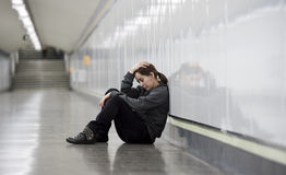Young sad woman in pain alone and depressed at urban subway tunn Royalty Free Stock Image