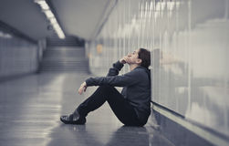 Young sad woman in pain alone and depressed at urban subway tunn Stock Photos