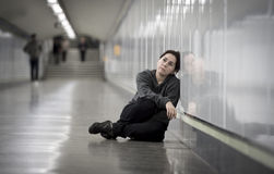 Young sad woman in pain alone and depressed at urban subway tunnel ground worried suffering depression Stock Photos