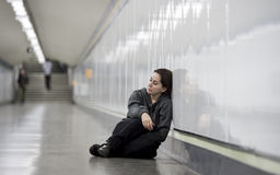 Young sad woman in pain alone and depressed at urban subway tunnel ground worried suffering depression Royalty Free Stock Photo