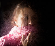 Young sad woman portrait behind the window in the rain with rain drops on it Stock Photo