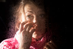 Young sad woman portrait behind the window in the rain with rain drops on it Royalty Free Stock Photo