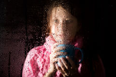 Young sad woman portrait behind the window in the rain with rain drops on it. girl holding a cup of hot drink Royalty Free Stock Photography