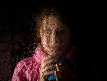 Young sad woman portrait behind the window in the rain with rain drops on it. girl holding a cup of hot drink Stock Images