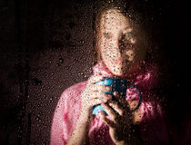 Young sad woman portrait behind the window in the rain with rain drops on it. girl holding a cup of hot drink Royalty Free Stock Photo