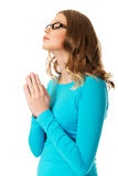 Young sad woman praying holding clasp hands. Teenage woman praying with clenched hands Royalty Free Stock Image