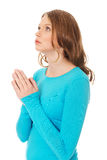 Young sad woman praying holding clasp hands. Teenage woman praying with clenched hands Royalty Free Stock Photography