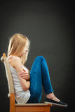 Young sad woman sitting on chair Stock Photos