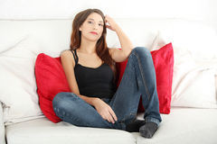 Young sad woman sitting on sofa Stock Images