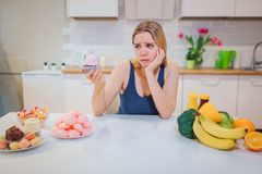 Young sad woman with sweet cake in one hand choosing between healthy and unhealthy food in the kitchen. Difficult choice stock images