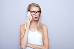 Young sad woman using mobile phone. Royalty Free Stock Photos