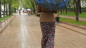 Young sad woman is walking in the rain in the park. stock video footage