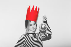 Young sad woman on white background at party, wearing stripped dress and red paper crown, carnival disco ball party Royalty Free Stock Photography