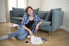 Young sad worried and desperate woman banking and accounting hom. E monthly and credit card expenses on living room floor doing  paperwork in living cost stress Stock Photo