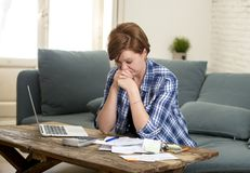 Young sad worried and desperate woman banking and accounting home monthly and credit card expenses with computer laptop. Doing  paperwork in living cost stress Royalty Free Stock Images