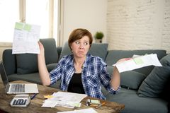 Young sad worried and desperate woman banking and accounting home monthly and credit card expenses with computer laptop. Doing  paperwork in living cost stress Royalty Free Stock Image