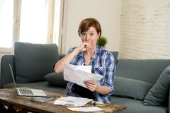 Young sad worried and desperate woman banking and accounting home monthly and credit card expenses with computer laptop. Doing  paperwork in living cost stress Royalty Free Stock Photo