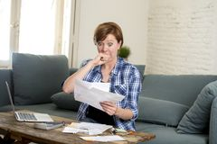 Young sad worried and desperate woman banking and accounting home monthly and credit card expenses with computer laptop. Doing  paperwork in living cost stress Stock Photography
