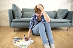 Young sad worried and desperate woman banking and accounting home monthly and credit card expenses on living room floor Stock Image