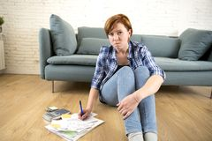Young sad worried and desperate woman banking and accounting home monthly and credit card expenses on living room floor Royalty Free Stock Photo