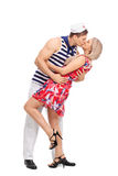 Young sailor kissing his girlfriend. Full length profile shot of a young sailor kissing his girlfriend isolated on white background royalty free stock images