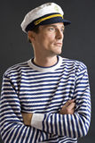 Young sailor man with white sailor hat. On grey background Royalty Free Stock Images