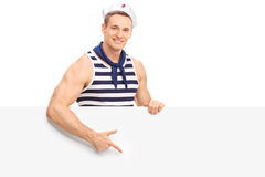 Young sailor pointing on a blank signboard. Young male sailor pointing on a blank signboard with his finger and looking at the camera  on white background Stock Photography