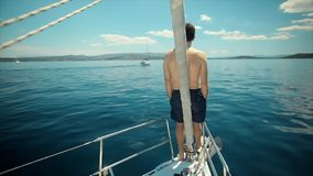 Young Sailor relaxing on the vacation sailboat yacht. Young Sailor relaxing happily on the vacation sailboat yacht having a rest on summer boat over blue ocean stock video footage