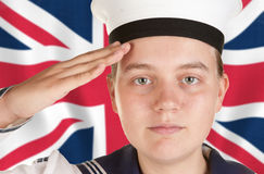 Young sailor saluting in front of union jack. Young female sailor saluting in front the union jack Royalty Free Stock Photos