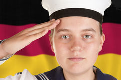 Young sailor saluting isolated white background. Young female sailor saluting in front of german flag Stock Photo