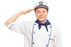 Young sailor saluting towards the camera. Cheerful young male sailor saluting towards the camera and smiling isolated on white background Stock Photo
