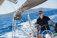 Young sailor skipper manages sailing vessel during regatta race Stock Image